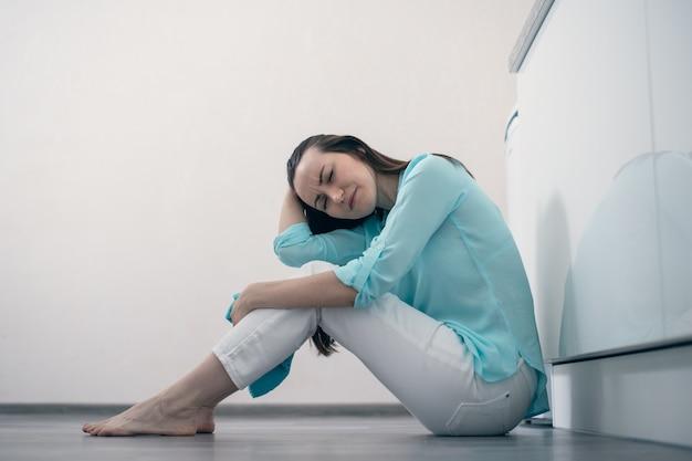 Mädchen mit dem dunklen haar, das auf dem boden im raum sitzt, seinen kopf und das weinen, die trauer des abschieds, das ende der beziehung hält Premium Fotos