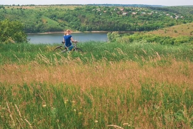 Mädchen mit dem fahrrad am ufer des flusses. ein mädchen sitzt auf einem fahrrad in der nähe eines zeltes auf dem fahrrad. das t von reisen und freiheit. Premium Fotos