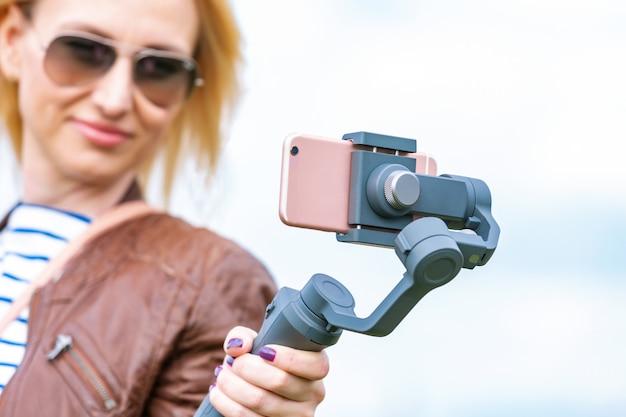 Mädchen mit dem telefon auf dem stabilisator führt den videoblog. sie nimmt sich mit der kamera smartphone Premium Fotos