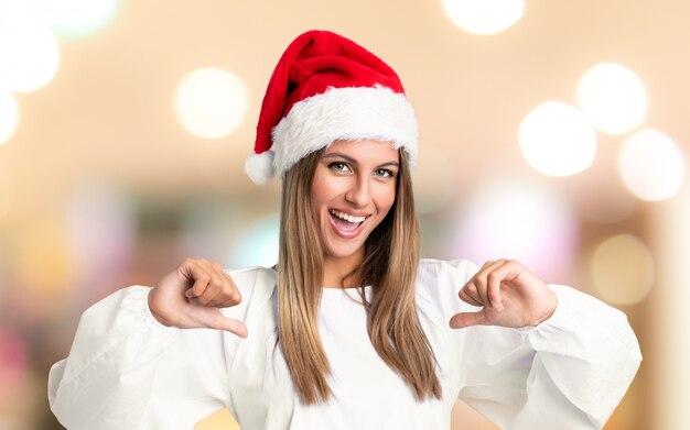 Mädchen mit dem weihnachtshut stolz und über unfocused hintergrund selbstzufrieden Premium Fotos