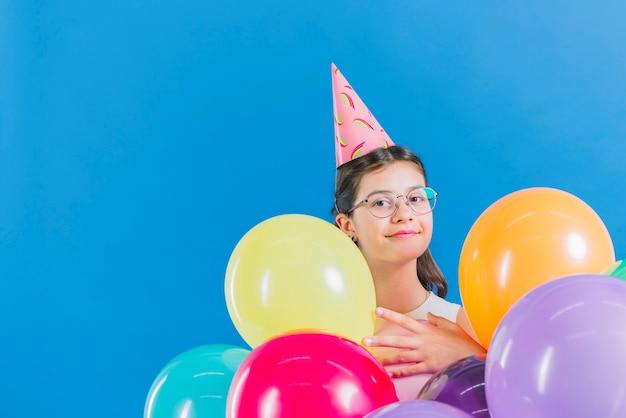 Mädchen mit den bunten ballonen, die kamera auf blauem hintergrund betrachten Kostenlose Fotos