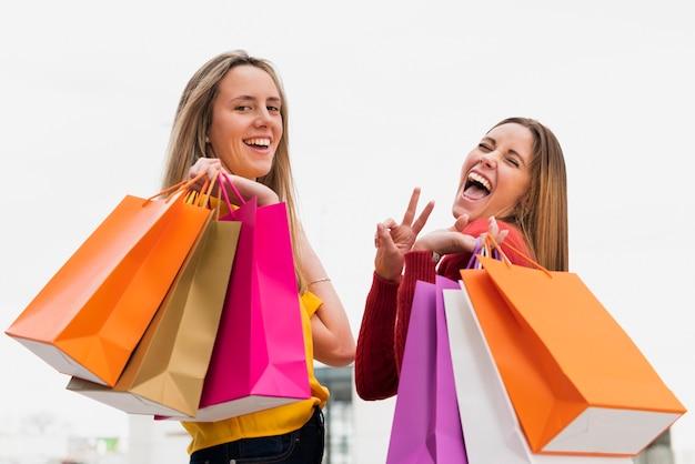 Mädchen mit den einkaufstaschen, die kamera betrachten Kostenlose Fotos
