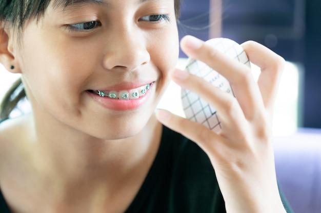 Mädchen mit den klammerzähnen, die zum spiegel säubert ihre zähne schauen Premium Fotos