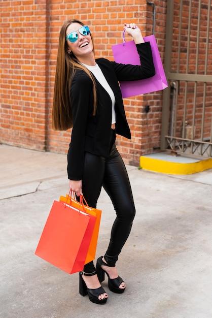 Mädchen mit der sonnenbrille, die einkaufstaschen hält Kostenlose Fotos
