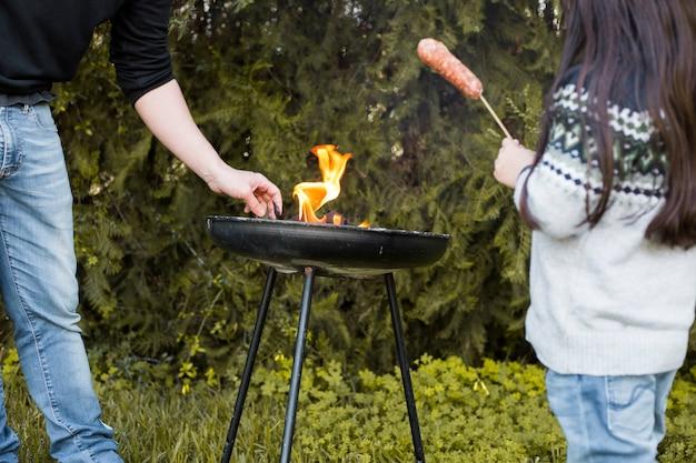 Mädchen mit der wurst, die nahe ihrem vater grillen auf tragbarem grill steht Kostenlose Fotos