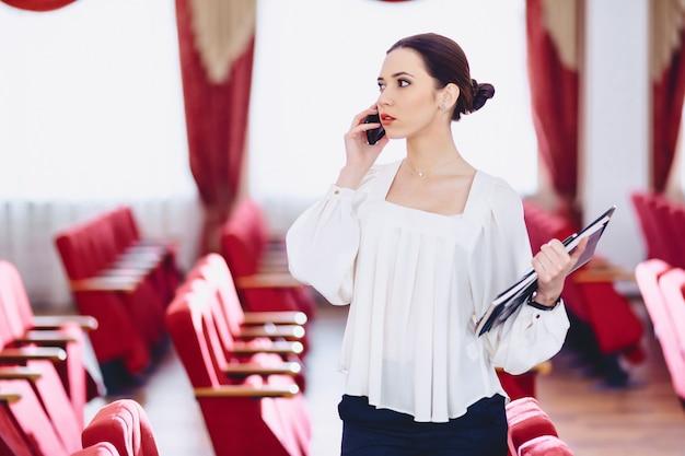 Mädchen mit dokumenten spricht per telefon Premium Fotos
