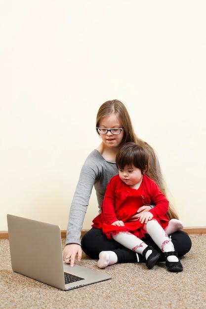Mädchen mit down-syndrom hält kind beim betrachten des laptops Kostenlose Fotos