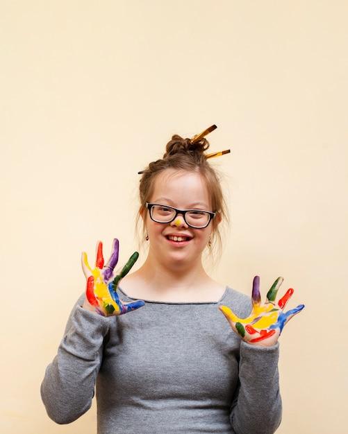 Mädchen mit down-syndrom posiert, während bunte palmen zeigen Premium Fotos