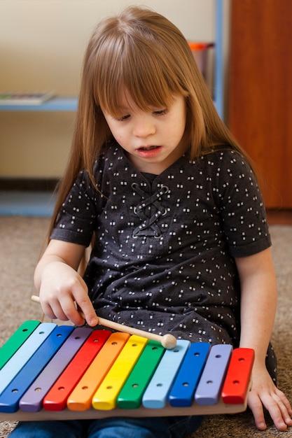 Mädchen mit down-syndrom spielt mit xylophon Kostenlose Fotos