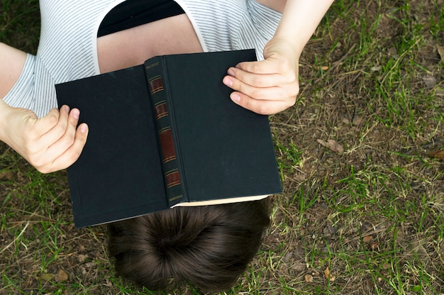 Mädchen mit einem buch liegt auf dem gras, draufsicht Premium Fotos