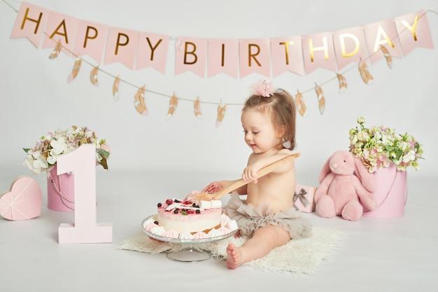 Mädchen mit einem geburtstagskuchen, 1-jährige babyfotosession Premium Fotos