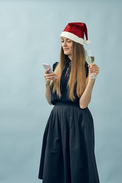 Mädchen mit einem glas champagner und einem weihnachtsmannhut Premium Fotos