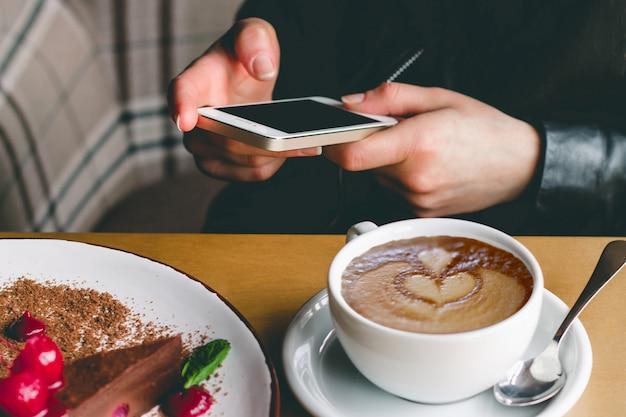 Mädchen mit einem handy, einem kaffee und einem kuchen in einem café. Premium Fotos