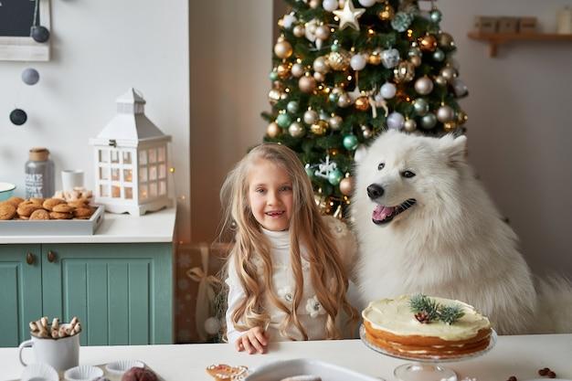 Mädchen mit einem hund nahe dem weihnachtsbaum auf dem weihnachtshintergrund Premium Fotos
