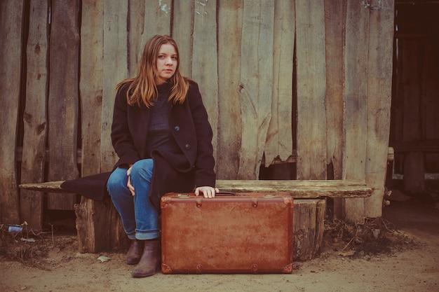 Mädchen mit einem koffer auf der bank gegen den hintergrund des alten zauns Premium Fotos