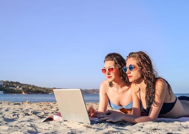 Mädchen mit einem laptop am strand Premium Fotos