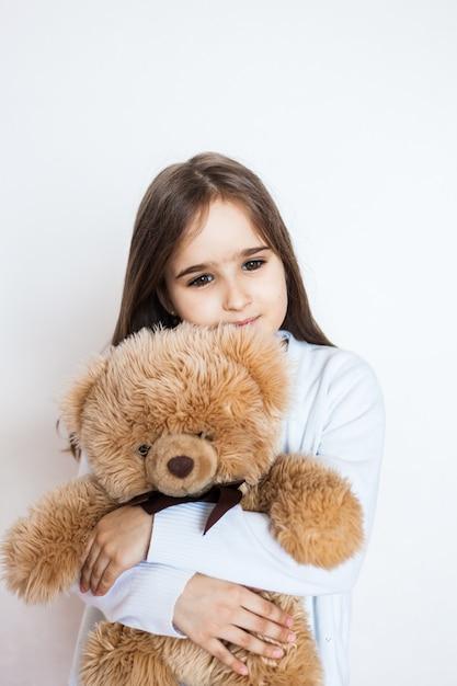Mädchen mit einem lieblings-teddybären, kindheit und fürsorge, familie und freunden. mädchen, das spielzeug spielt und umarmt Premium Fotos