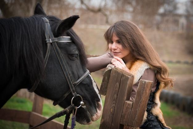 Mädchen mit einem pferd auf einer ranch an einem bewölkten tag des herbstes. Premium Fotos