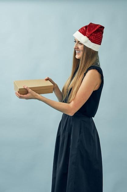 Mädchen mit einer geschenkbox in ihren händen und einem weihnachtsmannhut tragend Premium Fotos