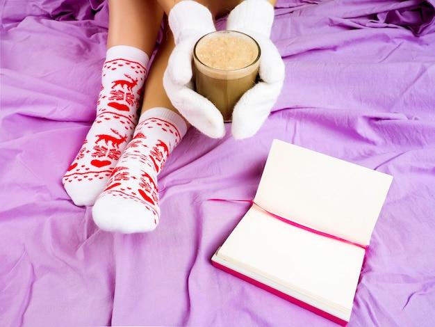 Mädchen mit einer tasse kaffee, nächstes buch, weihnachtseinstellung, socken für weihnachten Premium Fotos