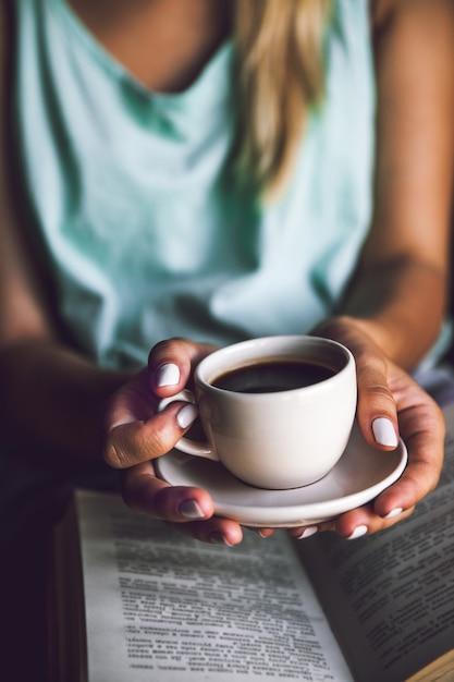 Mädchen mit einer tasse kaffee und einem buch. wacht auf, morgen, pause, hobbys Premium Fotos