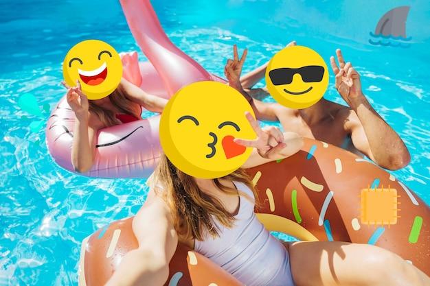 Mädchen mit emoji-gesichtern am pool Kostenlose Fotos