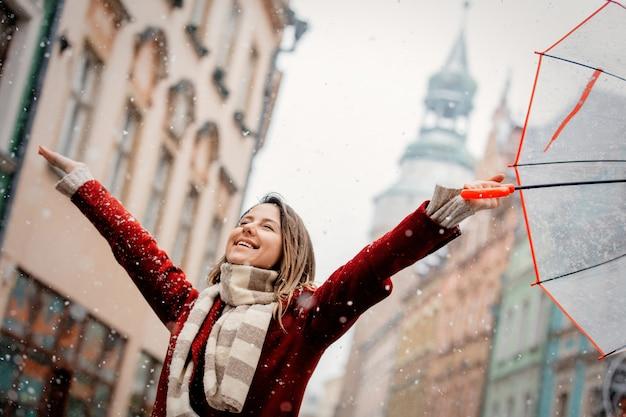 Mädchen mit fallendem aufenthalt des weißen schnees des regenschirmes auf stadtstraße Premium Fotos