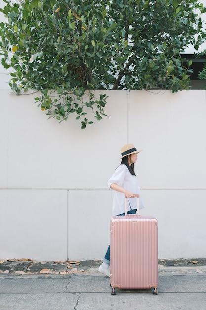 Mädchen mit gepäck auf der straße spazieren Kostenlose Fotos