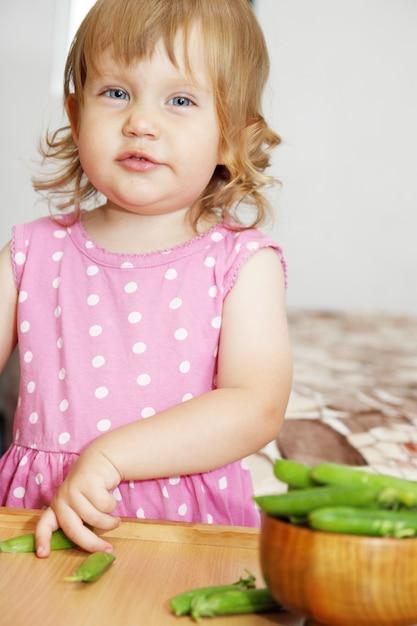 Mädchen mit grünen erbsen Premium Fotos