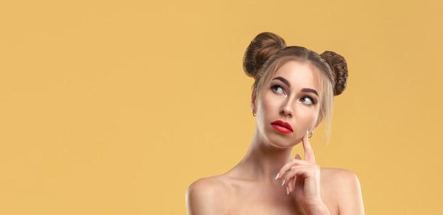 Mädchen mit haarknoten, die rotes kleid tragen smartphone tragen und mit kopienraum auf gelber wand denken Premium Fotos