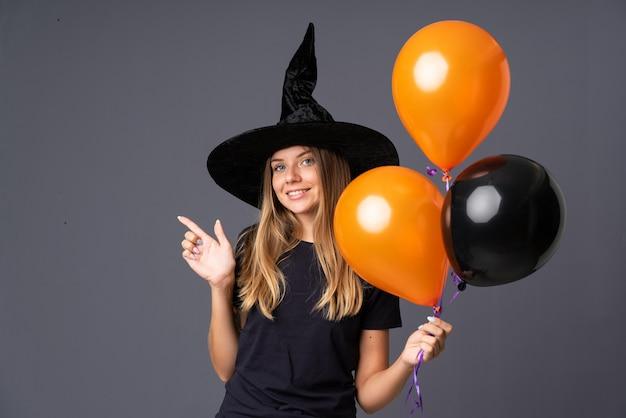 Mädchen mit hexenkostüm für halloween-party und zeigen auf die seite Premium Fotos