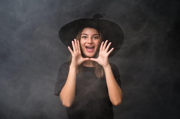 Mädchen mit hexenkostüm für halloween-partys über der lokalisierten dunklen wand, die mit dem breiten mund schreit, öffnen sich Premium Fotos