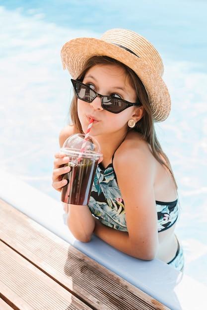Mädchen mit hut einen smoothie trinkend Kostenlose Fotos