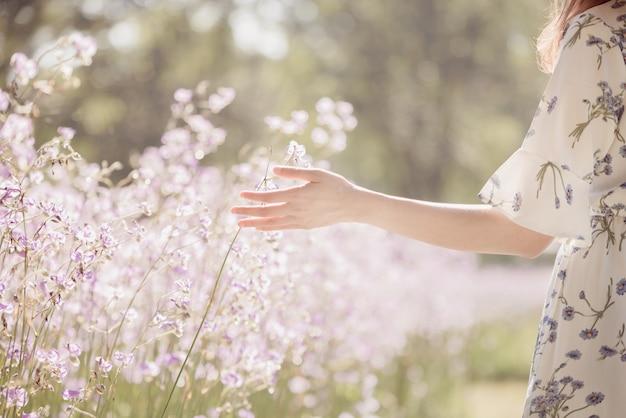 Mädchen mit ihrem rücken und strohhut auf einem gebiet von blumen, glückliche asiatische frau Premium Fotos