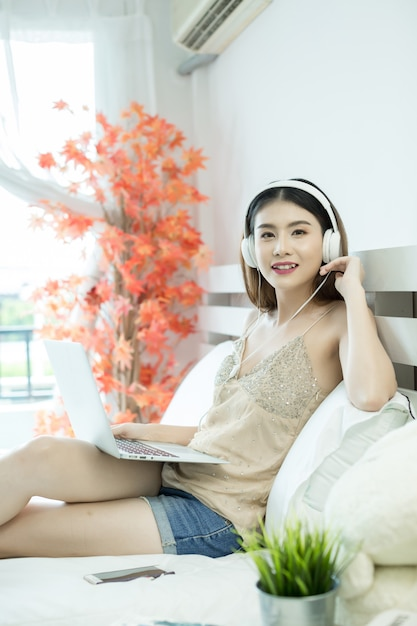 Mädchen mit kopfhörern hörend musik in einem laptop auf dem bett zu hause Kostenlose Fotos