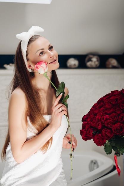 Mädchen mit langen haaren, die auf bad nach der morgendusche mit rose sitzen Premium Fotos