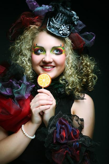 Mädchen mit mit kreativem make-up hält lutscher. puppenstil. Premium Fotos