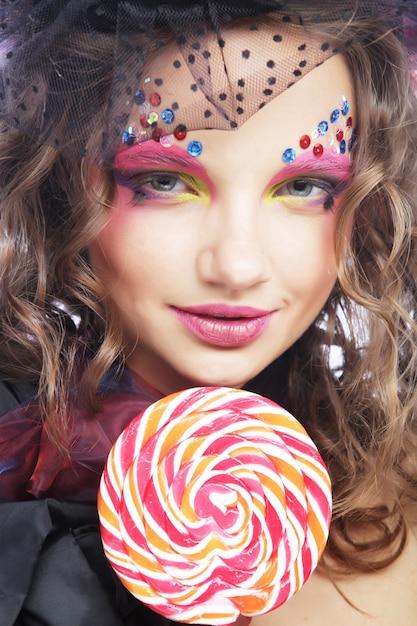 Mädchen mit mit kreativem make-up hält lutscher. Premium Fotos