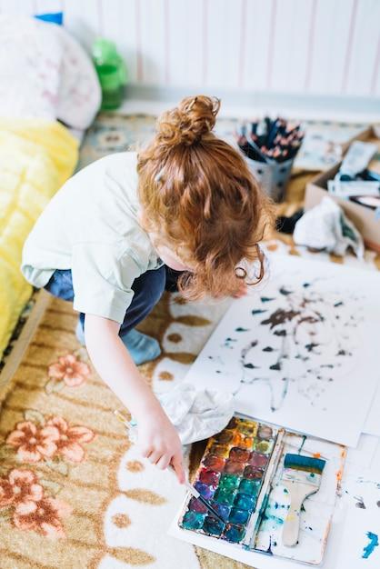 Mädchen mit pinsel nahe satz wasserfarben und papier, die auf boden sitzen Kostenlose Fotos