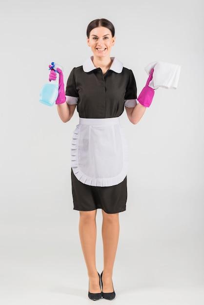 Mädchen mit reinigungsmittel und staubtuch lächelnd Kostenlose Fotos