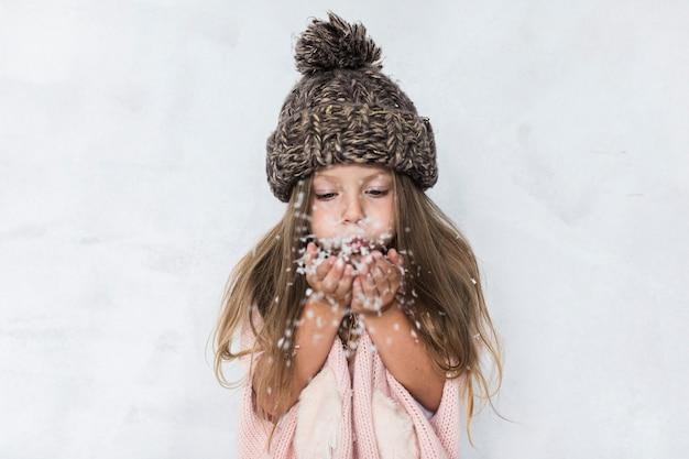 Mädchen mit schlagschnee des winterhutes Kostenlose Fotos