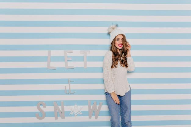 Mädchen mit slawischem aussehen im winterstrickpullover lächelt bescheiden und berührt ihr lockiges dunkles haar. frauenporträt im hellen innenraum Kostenlose Fotos