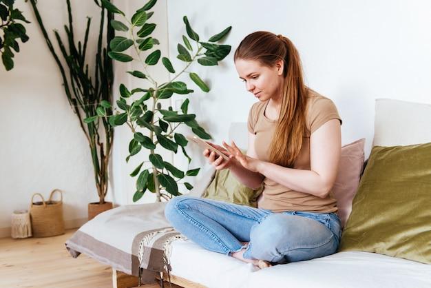 Mädchen mit smartphone zu hause auf sofa spaß gruß online sitzen Premium Fotos