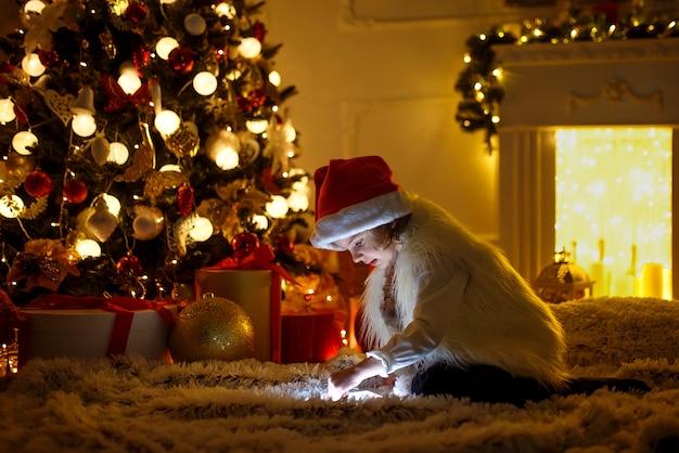 Mädchen mit tablette nahe weihnachtsbaum Premium Fotos