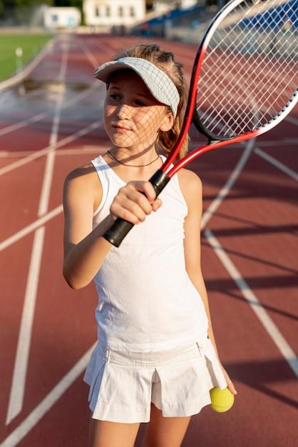 Mädchen mit tennisschläger und ball Kostenlose Fotos