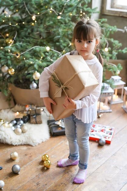 Mädchen mit weihnachtsbaum und geschenk Kostenlose Fotos