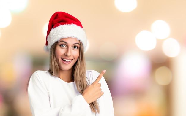 Mädchen mit weihnachtshut finger auf die seite über unfocused wand zeigend Premium Fotos