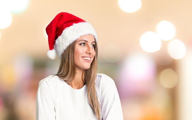 Mädchen mit weihnachtshut lachend über unfocused hintergrund Premium Fotos