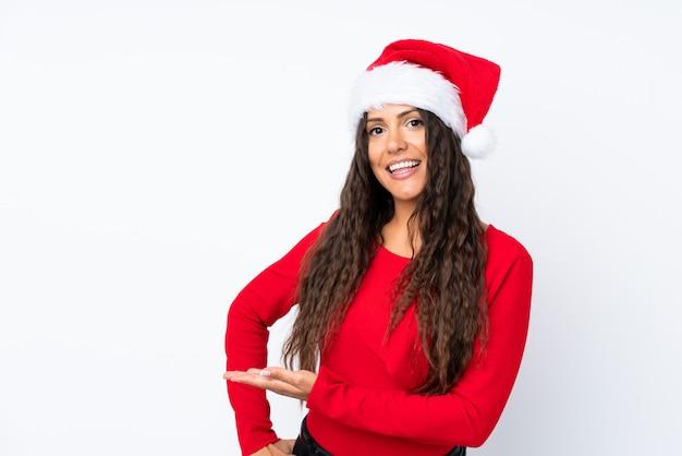Mädchen mit weihnachtshut über lokalisierten weißen erweiterungshänden zur seite, damit die einladung kommt Premium Fotos