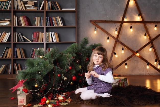 Mädchen nahe einem gefallenen weihnachtsbaum Premium Fotos